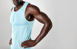 Muscular young african man standing with hands on hips. Cropped shot of muscular young african man standing with hands on hips against grey background with copy Stock Images