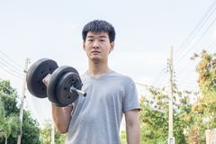 Muscular young asian man lifting weights in park. Healthy concept., sport concept stock photo