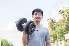 Muscular young asian man lifting weights in park. Healthy concept., sport concept stock photos