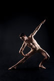 Muscular young athlete stretching in the black studio Stock Image