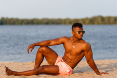 Muscular young athletic sexy man on the beach with a naked torso in underwear. Hot black beautiful guy, fitness model. Royalty Free Stock Photo