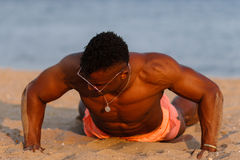 Muscular young athletic sexy man on the beach with a naked torso Royalty Free Stock Image