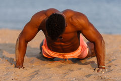 Muscular young athletic sexy man on the beach with a naked torso in underwear. Hot black beautiful guy, fitness model. Royalty Free Stock Images