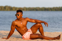 Muscular young athletic sexy man on the beach with a naked torso in underwear. Hot black beautiful guy, fitness model. Stock Photos