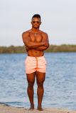Muscular young athletic man on the beach with a naked torso in underwear. Hot black beautiful guy, fitness model. Stock Photography