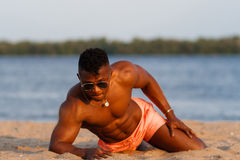 Muscular young athletic man on the beach with a naked torso in underwear. Hot black beautiful guy, fitness model. Stock Images