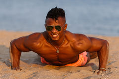Muscular young athletic sexy man on the beach with a naked torso in underwear. Hot black beautiful guy, fitness model. Stock Photo