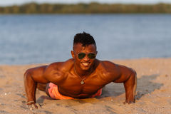 Muscular young athletic sexy man on the beach with a naked torso in underwear. Hot black beautiful guy, fitness model. Stock Photography