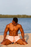Muscular young athletic sexy man on the beach with a naked torso in underwear. Hot black beautiful guy, fitness model with a rangy Royalty Free Stock Image