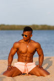 Muscular young athletic sexy man on the beach with a naked torso in underwear. Hot black beautiful guy, fitness model with a rangy Stock Image