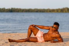 Muscular young athletic sexy man on the beach with a naked torso in underwear. Hot black beautiful guy, fitness model with a rangy Royalty Free Stock Photo
