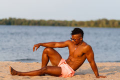 Muscular young athletic sexy man on the beach with a naked torso in underwear. Hot black beautiful guy, fitness model with a rangy Royalty Free Stock Photography