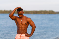 Muscular young athletic sexy man on the beach with a naked torso in underwear. Hot black beautiful guy, fitness model with a rangy Royalty Free Stock Photos