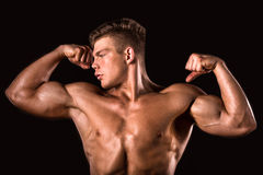 Muscular young bodybuilder man, upper body. Muscular young bodybuilder man showing his biceps on a black background Stock Photography