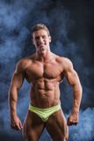 Muscular young bodybuilder in relaxed pose Royalty Free Stock Images