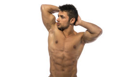 Muscular young bodybuilder showing biceps and ripped abs. Cute muscular ripped young bodybuilder with hands behind his head, looking away. Isolated on white Stock Photo