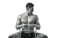 Muscular young bodybuilder sitting on chair Royalty Free Stock Photos