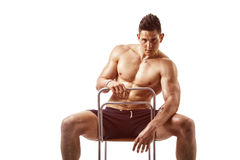 Muscular young bodybuilder sitting on chair Stock Images