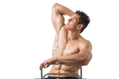 Muscular young bodybuilder sitting on chair Stock Photography