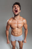 Muscular young brunette man wearing underwear shouting Royalty Free Stock Images