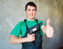 Muscular young builder, sing big finger. Royalty Free Stock Image