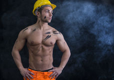 Muscular young construction worker shirtless. Wearing hardhat, dark background with smoke Stock Photos