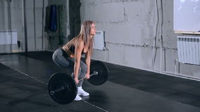 Muscular young fitness beautiful blonde girl lifting a weight cross fit in the gym. Muscular fitness beautiful blonde girl lifting a weight cross fit in the gym stock video footage