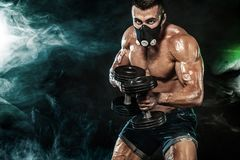 Muscular young fitness sports man, bodybuilder in training mask. Workout with dumbbell in fitness gym Royalty Free Stock Photo