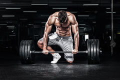 Muscular young fitness sports man workout with barbell in fitness gym. Athletic shirtless young sports man - fitness model with barbell in gym stock photography