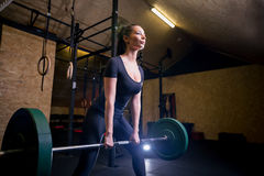 Muscular young fitness woman doing heavy deadlift exercise in gym stock photos