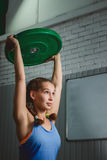 Muscular young fitness woman lifting a weight crossfit in the gym. Crossfit. Woman. Crossfit style Royalty Free Stock Images