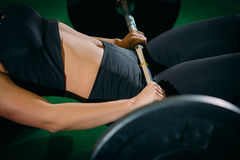 Muscular young fitness woman lifting a weight crossfit in the gym. Fitness woman deadlift barbell. Crossfit woman. Muscular young fitness woman lifting a weight Royalty Free Stock Photography