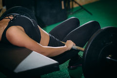 Muscular young fitness woman lifting a weight crossfit in the gym. Fitness woman deadlift barbell. Crossfit woman. Muscular young fitness woman lifting a weight Stock Photos