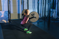 Muscular young fitness woman lifting a weight crossfit in the gym. Fitness woman deadlift barbell. Crossfit woman. Muscular young fitness woman lifting a weight Stock Photo