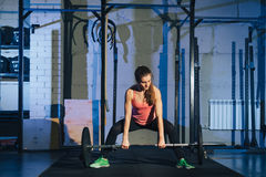 Muscular young fitness woman lifting a weight crossfit in the gym. Fitness woman deadlift barbell. The gym on the red. Wall is written SPORT. Crossfit woman Royalty Free Stock Images