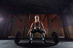 Muscular young fitness woman lifting a weight in the gym. Muscular young fitness woman lifting a weight crossfit in the gym. Fitness woman deadlift barbell Stock Photo