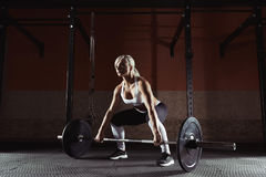 Muscular young fitness woman lifting a weight in the gym. Muscular young fitness woman lifting a weight crossfit in the gym. Fitness woman deadlift barbell Stock Photos