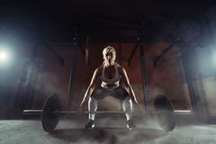 Muscular young fitness woman lifting a weight in the gym. Fitness woman deadlift barbell. Fitness woman Stock Image