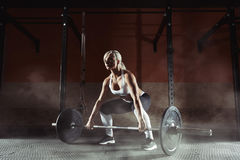Muscular young fitness woman lifting a weight in the gym. Fitness woman deadlift barbell. Fitness woman Stock Photo