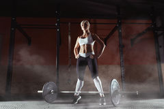 Muscular young fitness woman lifting a weight in the gym. Fitness woman deadlift barbell. Fitness woman Royalty Free Stock Images