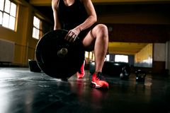 Muscular young woman putting heavy weights for exercise. Muscular young fitness woman putting heavy weights for exercise close up stock image