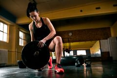 Muscular young woman putting heavy weights for exercise. Muscular young fitness woman putting heavy weights for exercise royalty free stock photography