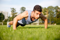 Muscular young guy doing push-ups in park on lawn Royalty Free Stock Image