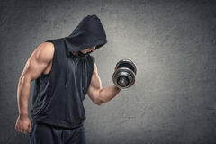 Muscular young guy in hoodie lifting a dumbbell to show his biceps Stock Photography