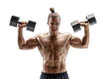 Muscular young guy working out with dumbbells. Royalty Free Stock Image