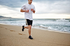 Muscular young jogger running on the beach along the sea. Morning jog, fitnes and healthily lifestyle royalty free stock images