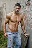 Muscular young latino man shirtless in jeans leaning on wall Stock Photography