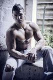 Muscular young latino man shirtless in jeans sitting Royalty Free Stock Photo