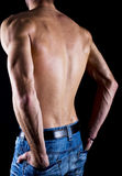 Muscular young male body on black background. Royalty Free Stock Photos