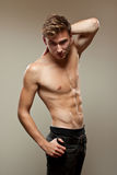 Muscular young man. Posing with bare chest; studio background Royalty Free Stock Photos